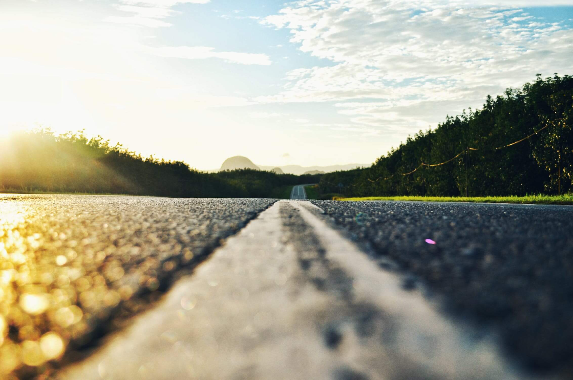 A ground-level view of the asphalt of a paved roadway, looking into hills on the horizon.