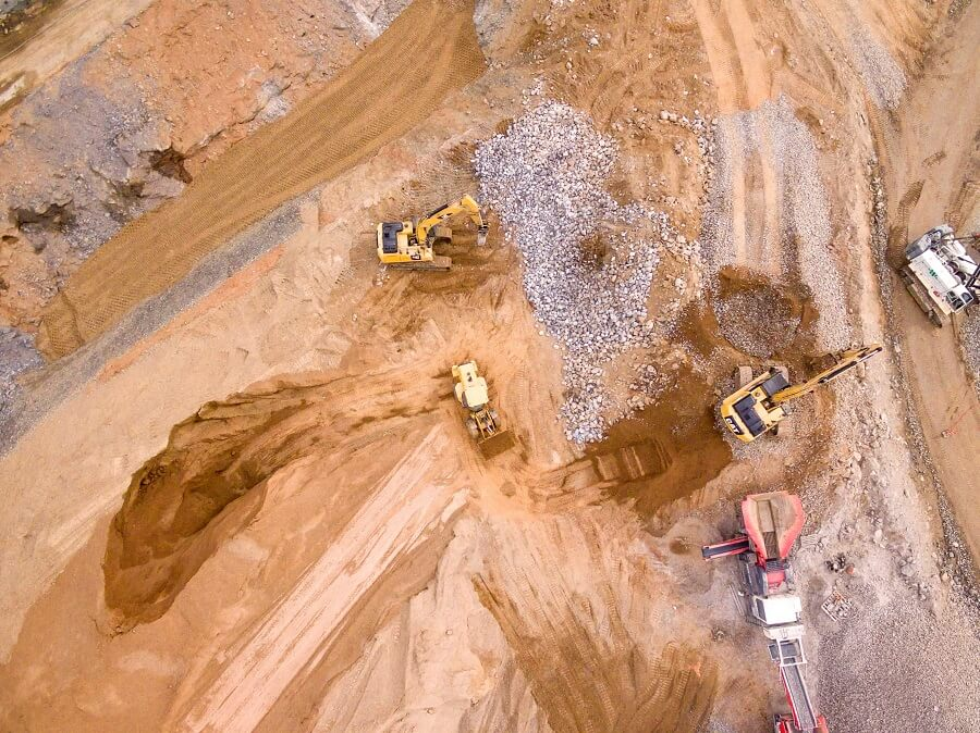 birds-eye-view of trucks in a quarry digging up stone