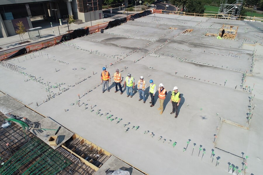 Group of men wearing construction vests stand on concrete foundation