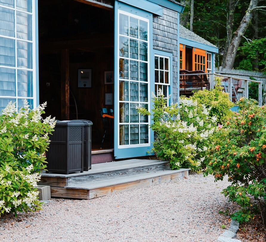 Blue home with french sliding door and gravel walkway