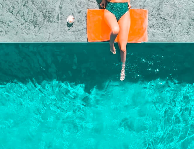 woman sits on the concrete deck of her pool