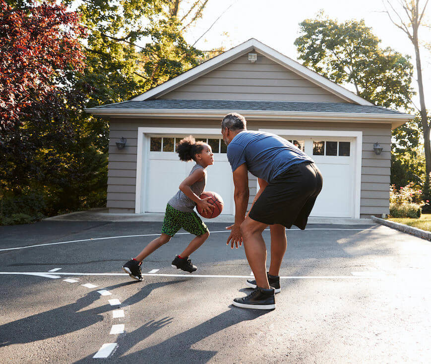 Father And Child Playing Basketball On Driveway At Home