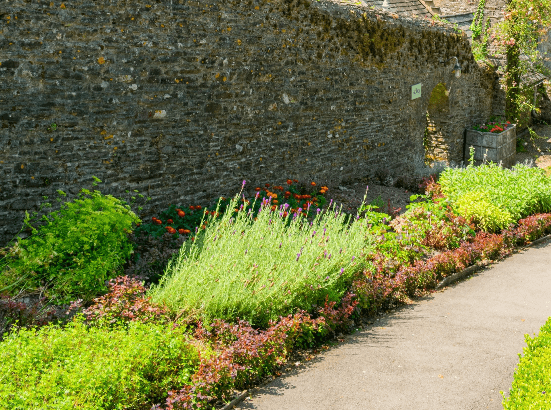 lush garden below an old, natural stone retaining wall
